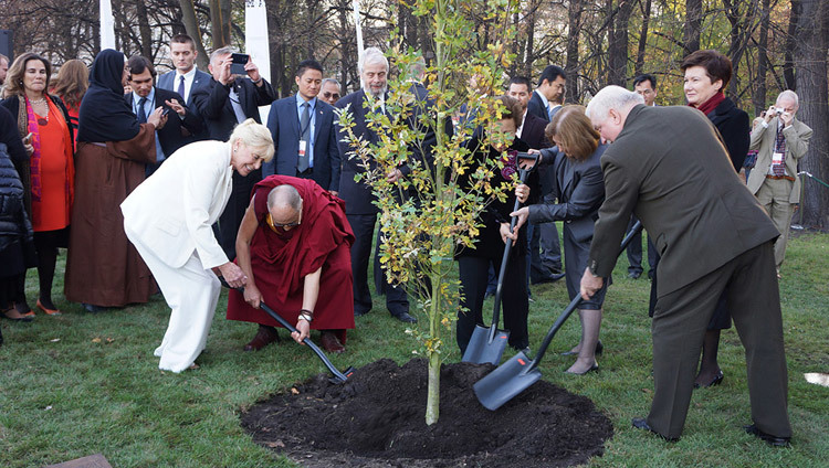Betty Williams, His Holiness the Dalai Lama, Shirin Ebadi, Mairead Maguire and Lech Walesa planting a tree after the 13th World Summit of Nobel Peace Laureates in Warsaw, Poland on October 23, 2013. (Photo by Jeremy Russell/OHHDL)